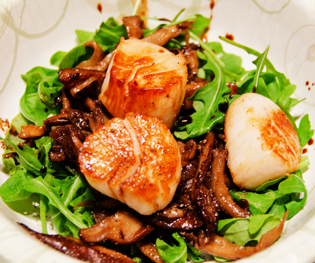 Seared scallops on a bed of baby greens with sauteed wild mushrooms.