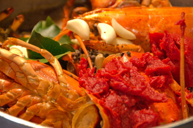 Roasted lobster shells and other ingredients go into the stockpot.