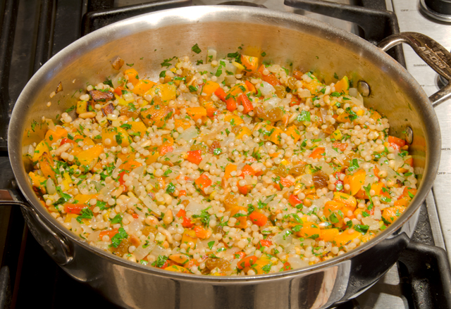 The vegetables are added back into the couscous.