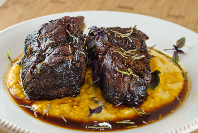Short ribs served on a bed of polenta.