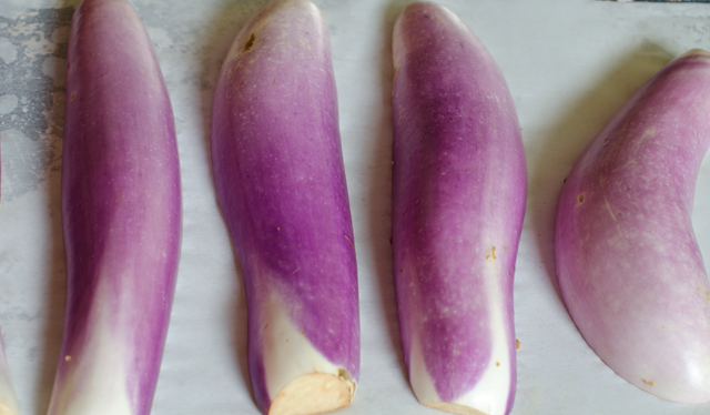 Place the eggplants cut side down on a parchment lined baking sheet.
