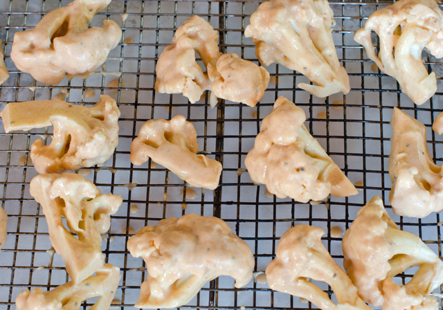 Dip cauliflower pieces in the batter. Place on a wire rack above the parchment lined baking tray for easy clean up.