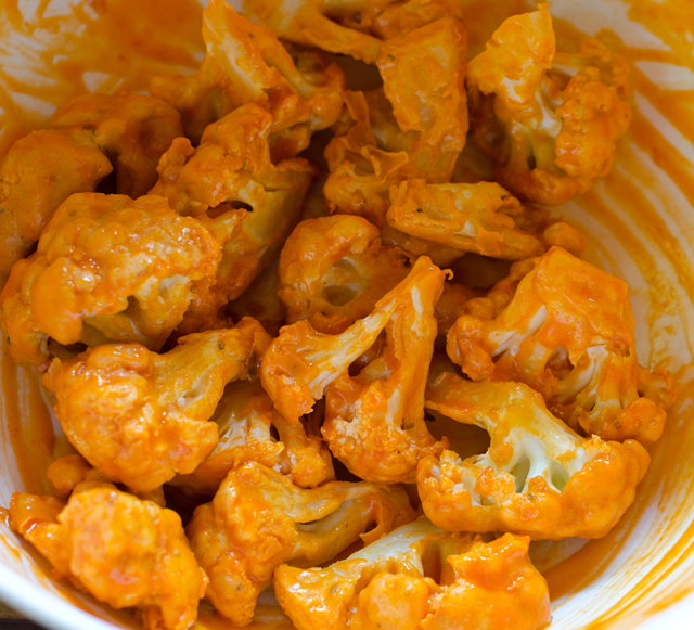 After the cauliflower has baked to a golden brown, mix with hot sauce and butter.